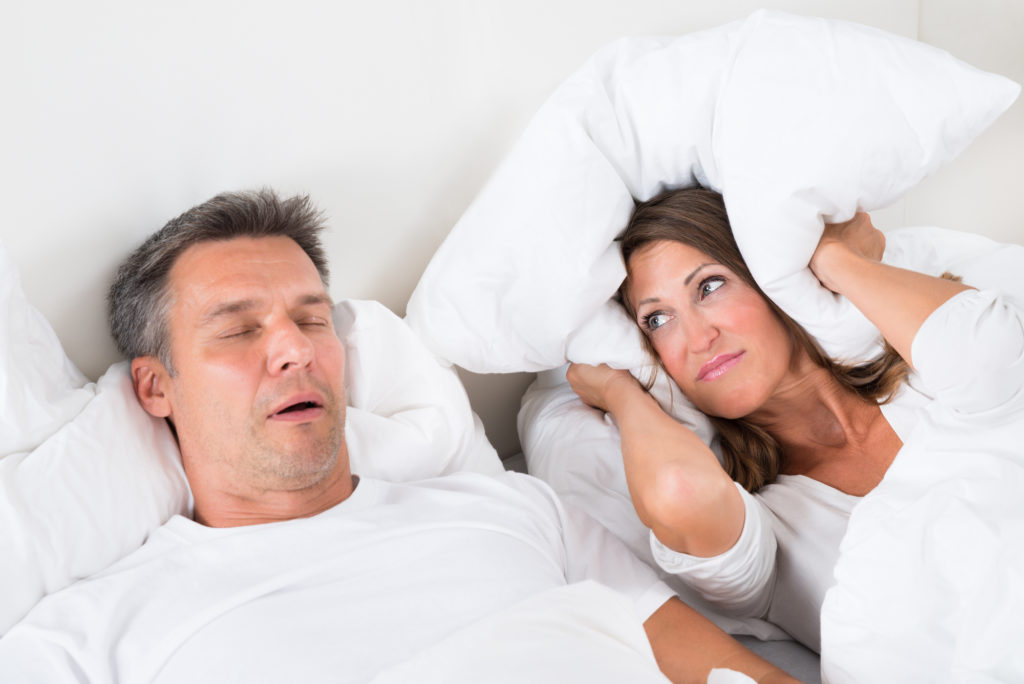 Image of woman covering her ears with a pillow because husband snores which is a symptom of sleep apnea.
