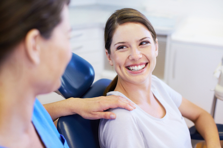 Woman smiling up at her dentist after learning about oral surgery options available at her Surrey BC dentist office.