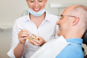 Dentist showing a patient how a dental bridge will restore the look and feel of his natural smile.